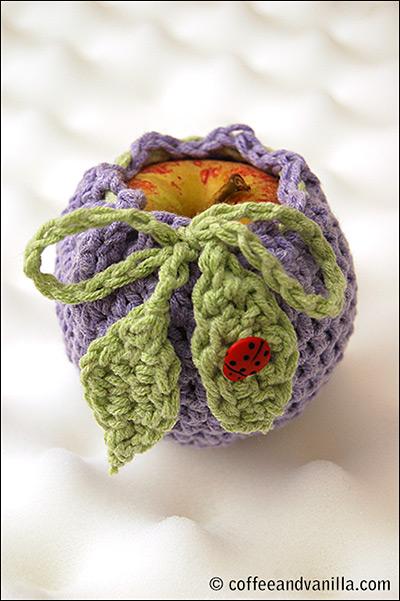 ladybug button on a crochet apple cosy